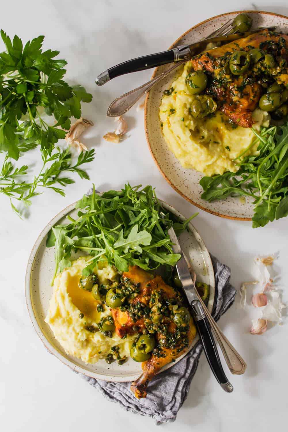 2 plates with chicken, mashed potatoes, and fresh arugula.
