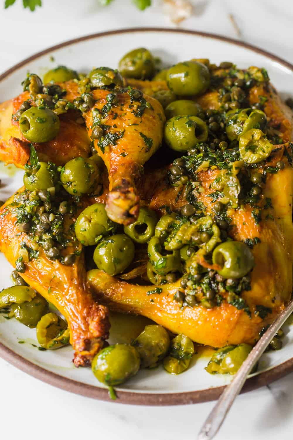 Close up of baked chicken quarters on a white plate with olives and capers on top.