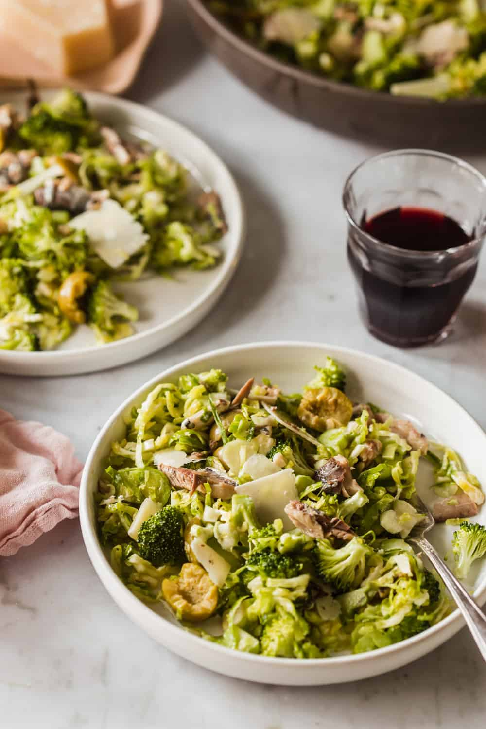 White bowls filled with salad and wine glass