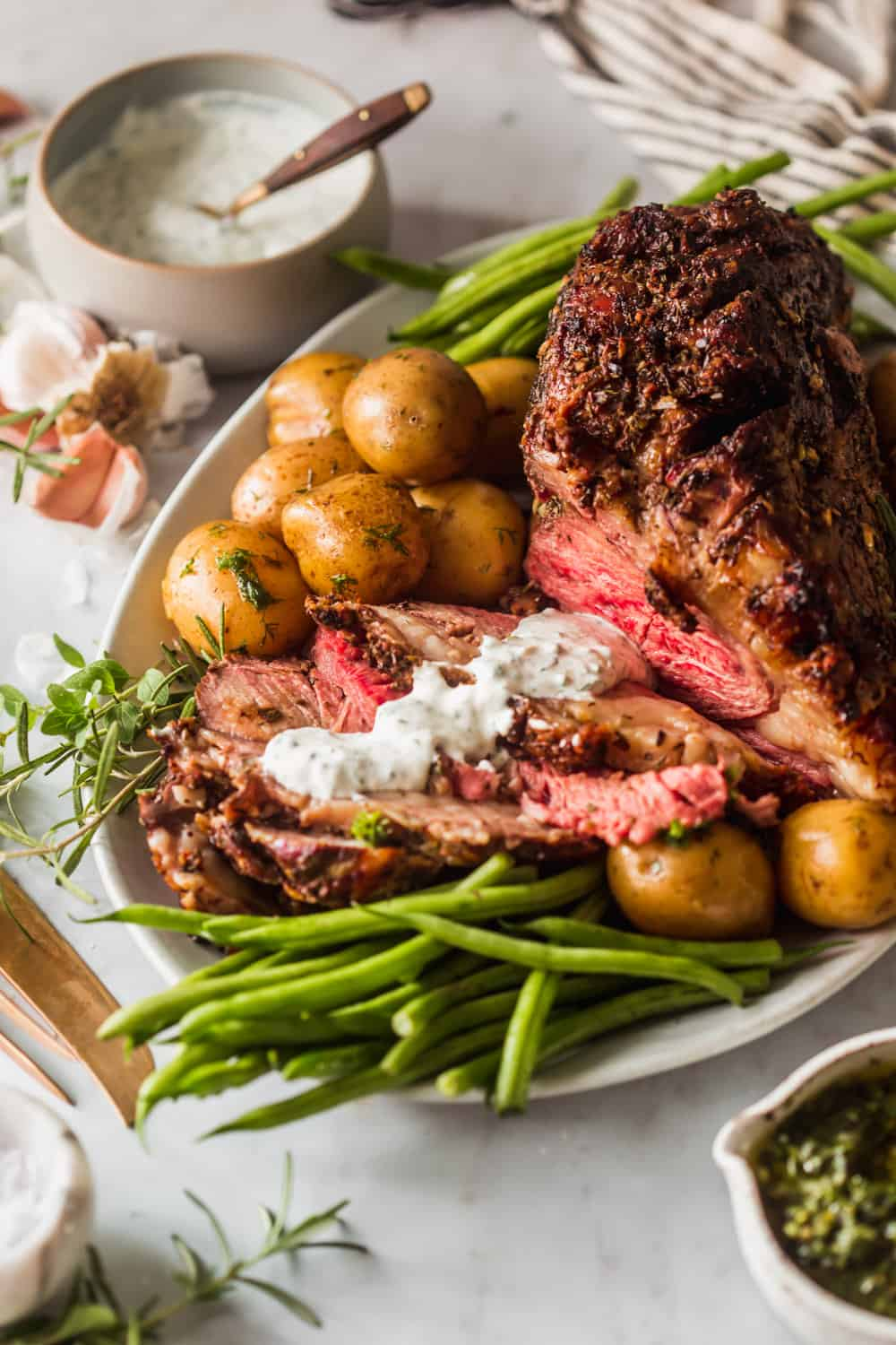 A sliced and cooked prime rib roast on a white serving plate with baby potatoes and green beans on the side