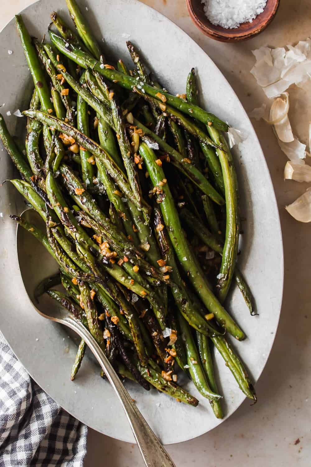 Large white serving dish full of cooked green beans
