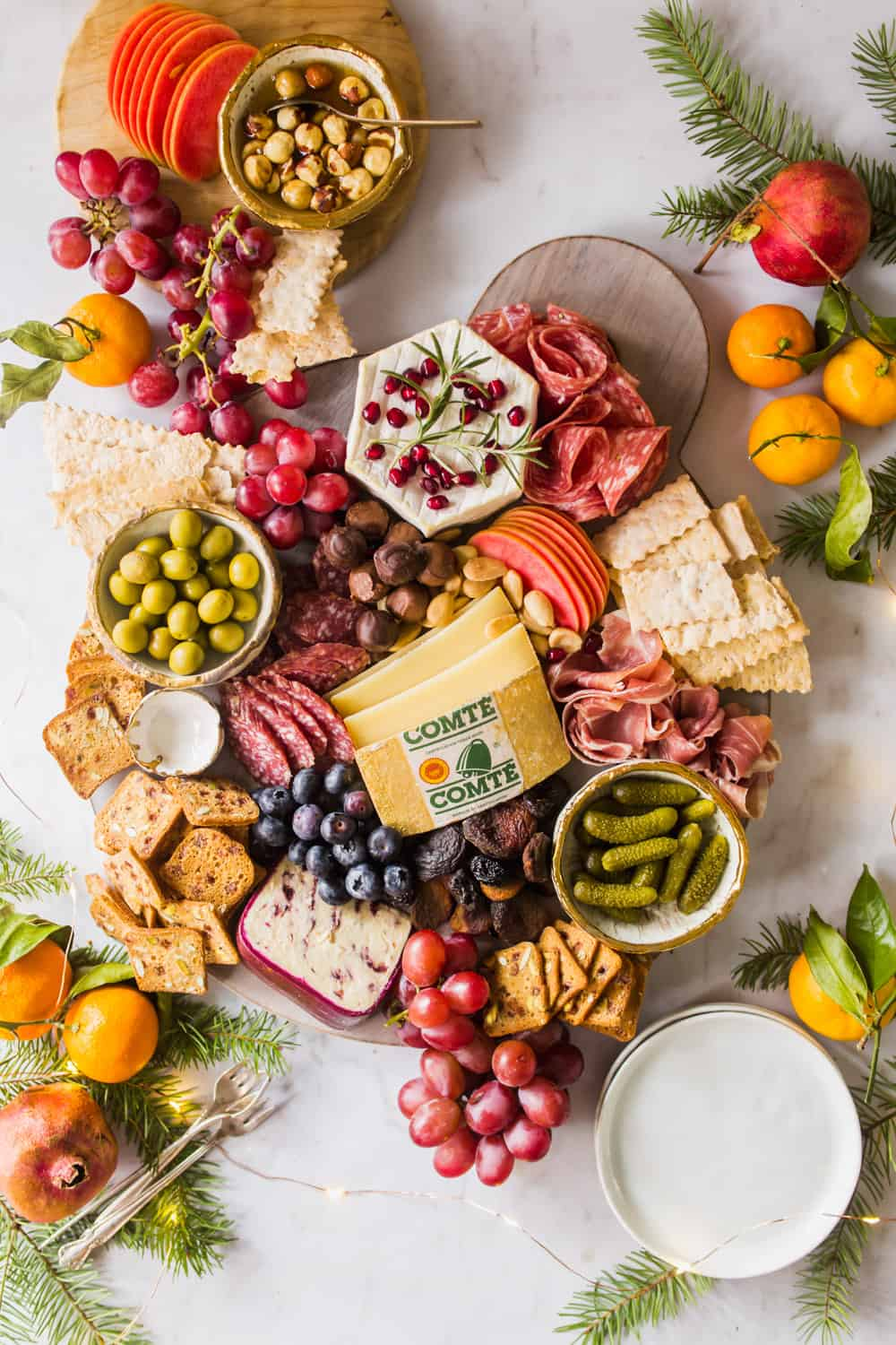 Overhead view of a large platter layered in cheese, meat, crackers, fruit, pickles, olives, and berries.