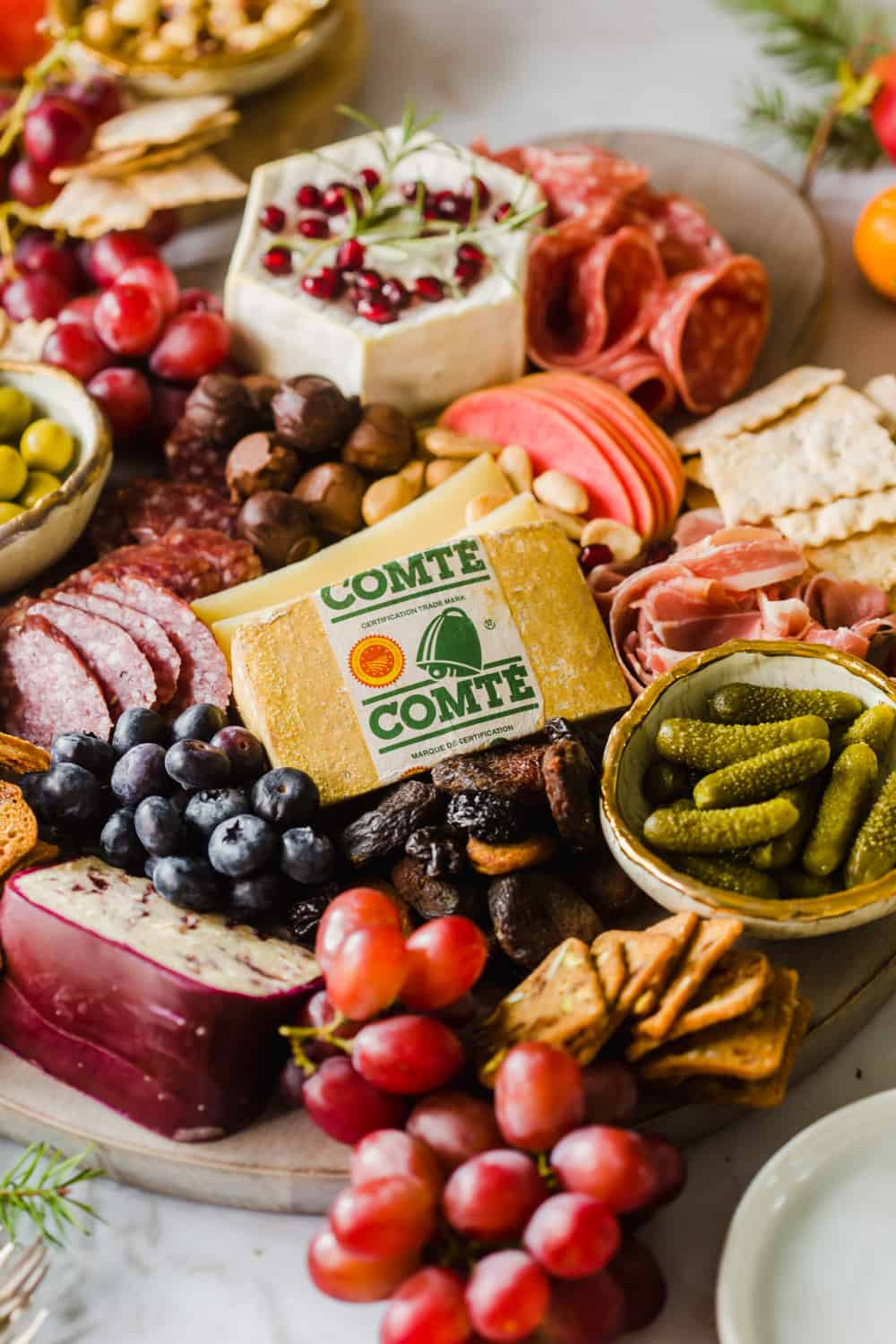 Close up of a large platter layered in Comte cheese, meat, fruit, crackers, and pickles.