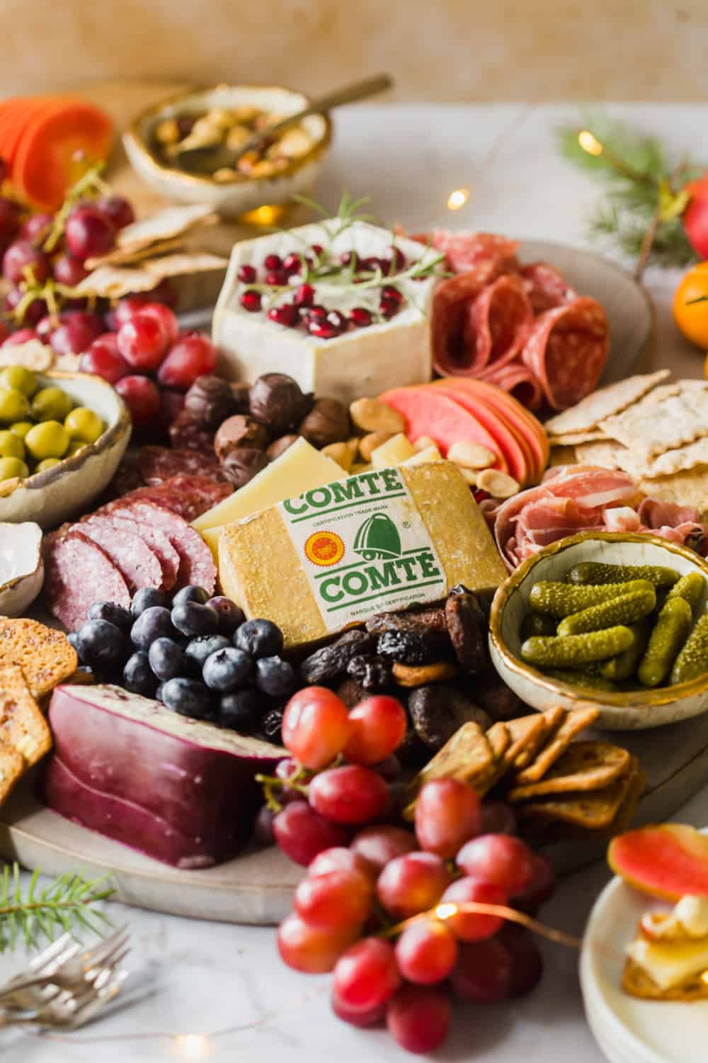 Close up of a large platter with lots of meats, cheeses, fruits, pickles, and crackers.