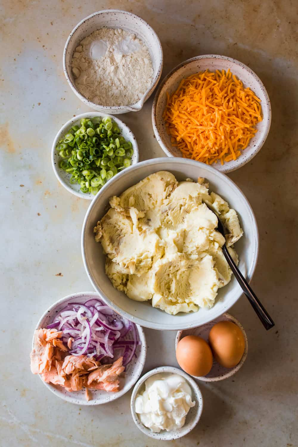 Mashed potatoes in a large white bowl. Cheese, scallions, onions, eggs, and flour in separate white bowls on the side.