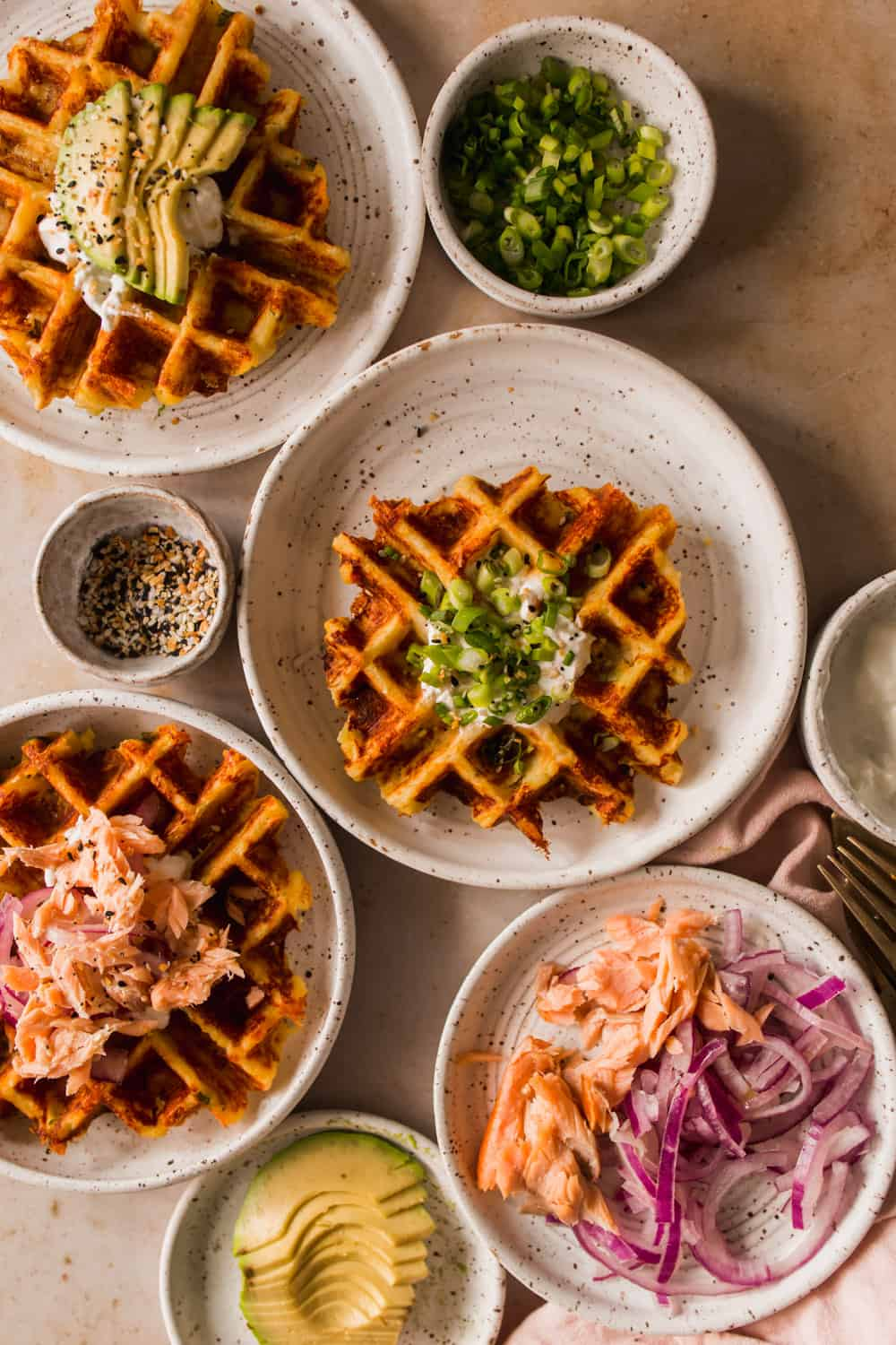 Cooked waffles on 3 white plates. Topping options in individual bowls on the side.