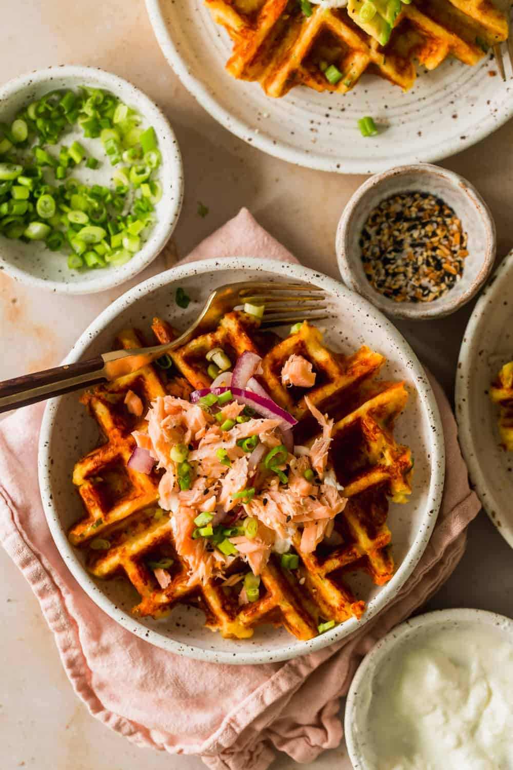 Close up of a cooked waffle with salmon and scallions on top.