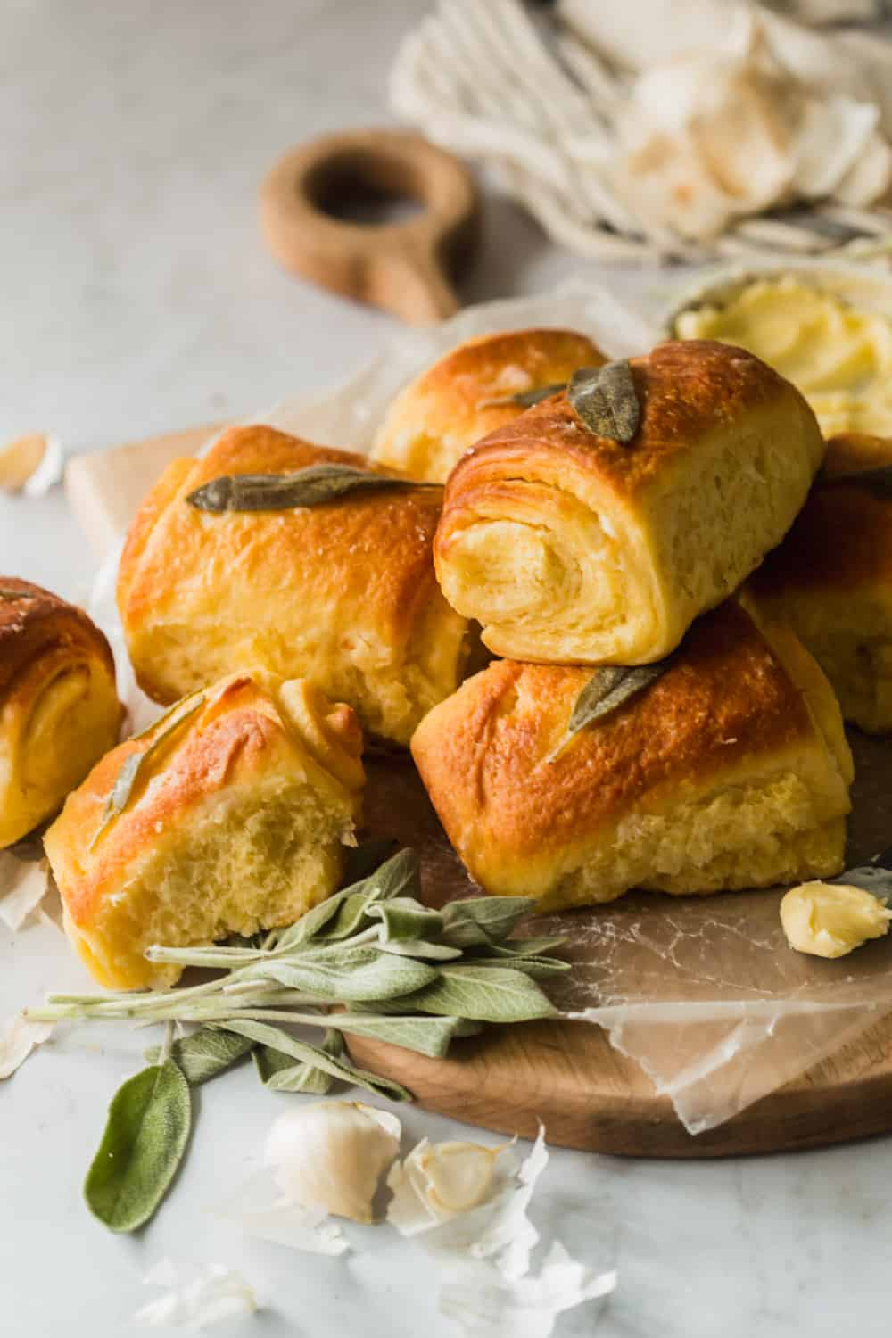 Close up of baked dinner rolls with fresh sage leaves