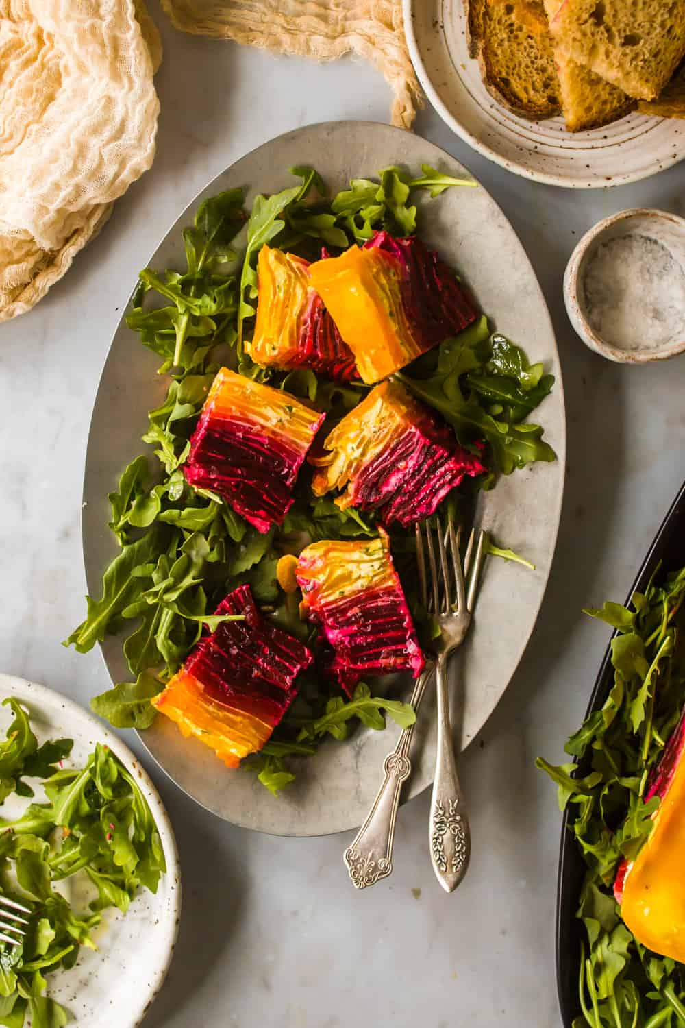 Slices of red and yellow beet terrine on top of arugula on a grey serving plate