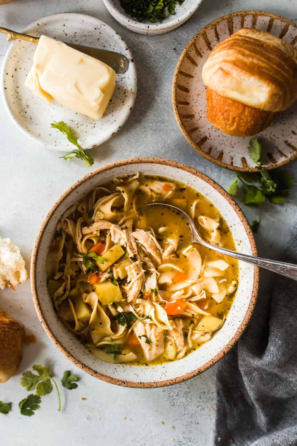 Large white and brown bowl with a spoon and chicken noodle soup