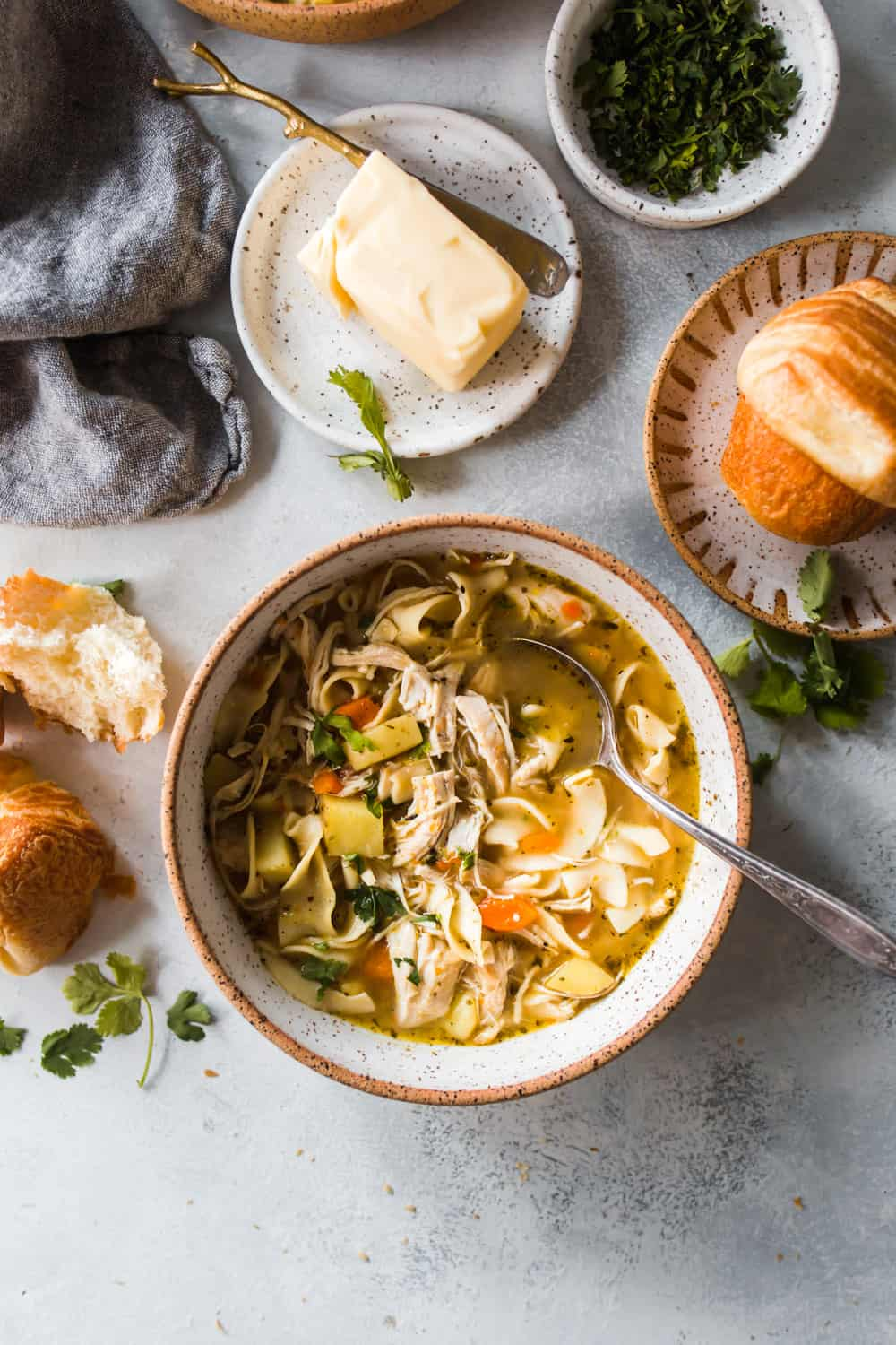 Large white and brown bowl holding a spoon and chicken noodle soup