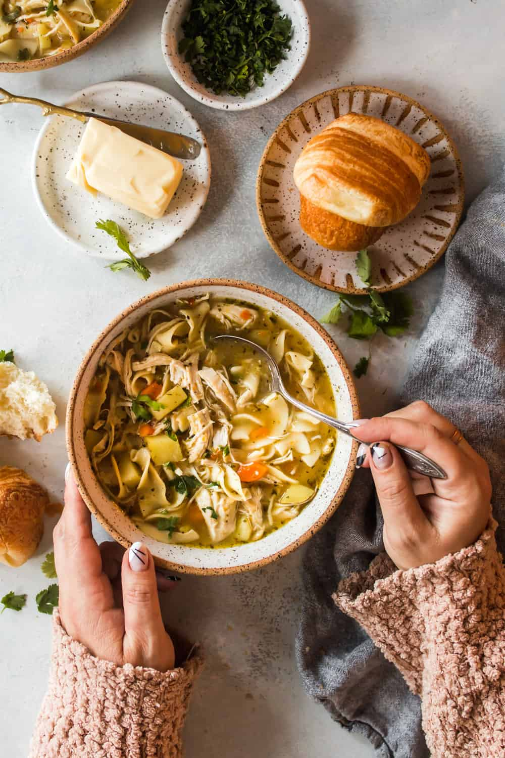Woman's hands taking a spoonful of chicken soup from a white bowl. Bread and butter on the side.
