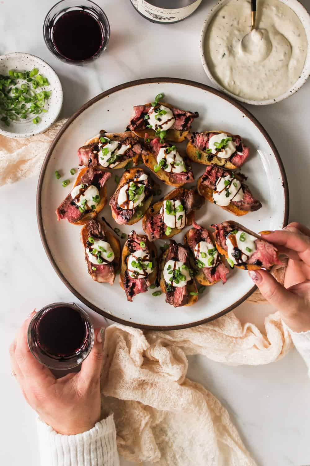 Woman's hand holding a crostini topped with sliced steak, white cheese sauce, and balsamic