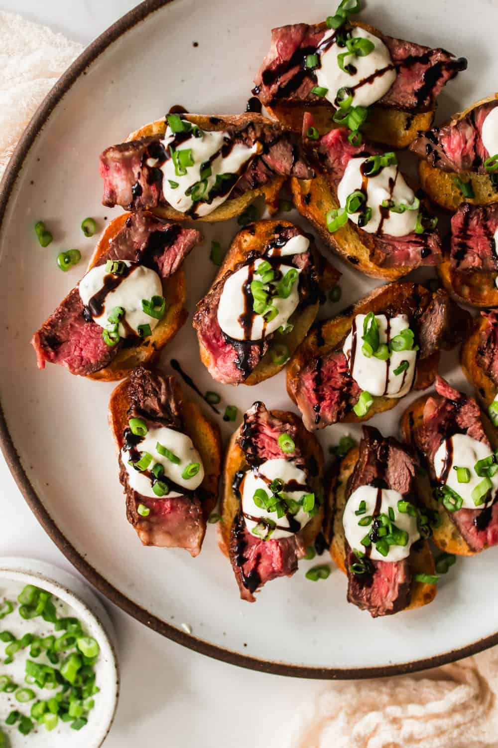 Steak and cream sauce on top of crostini on a white plate
