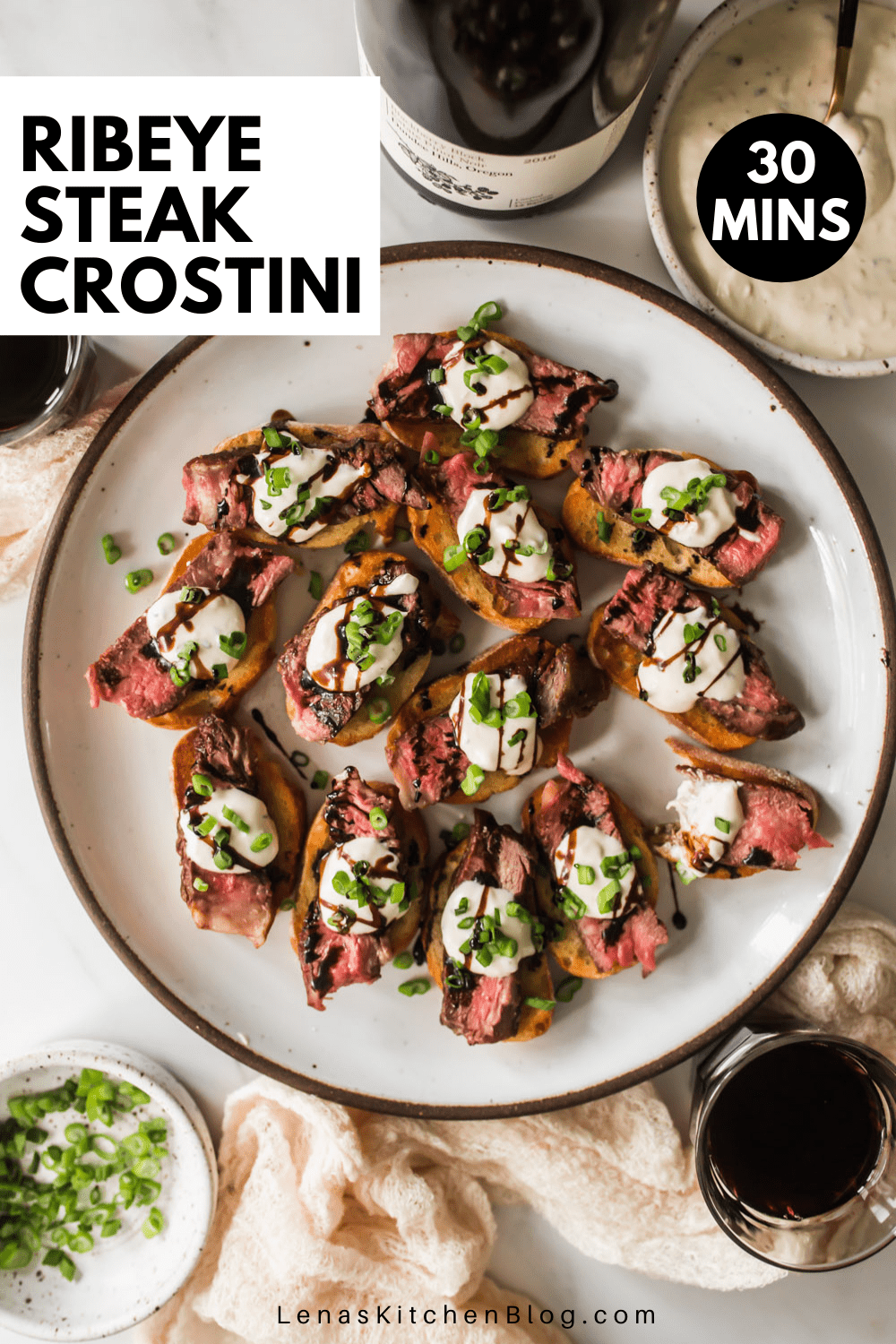 White plate with crostini topped with sliced steak, white cheese sauce, and balsamic