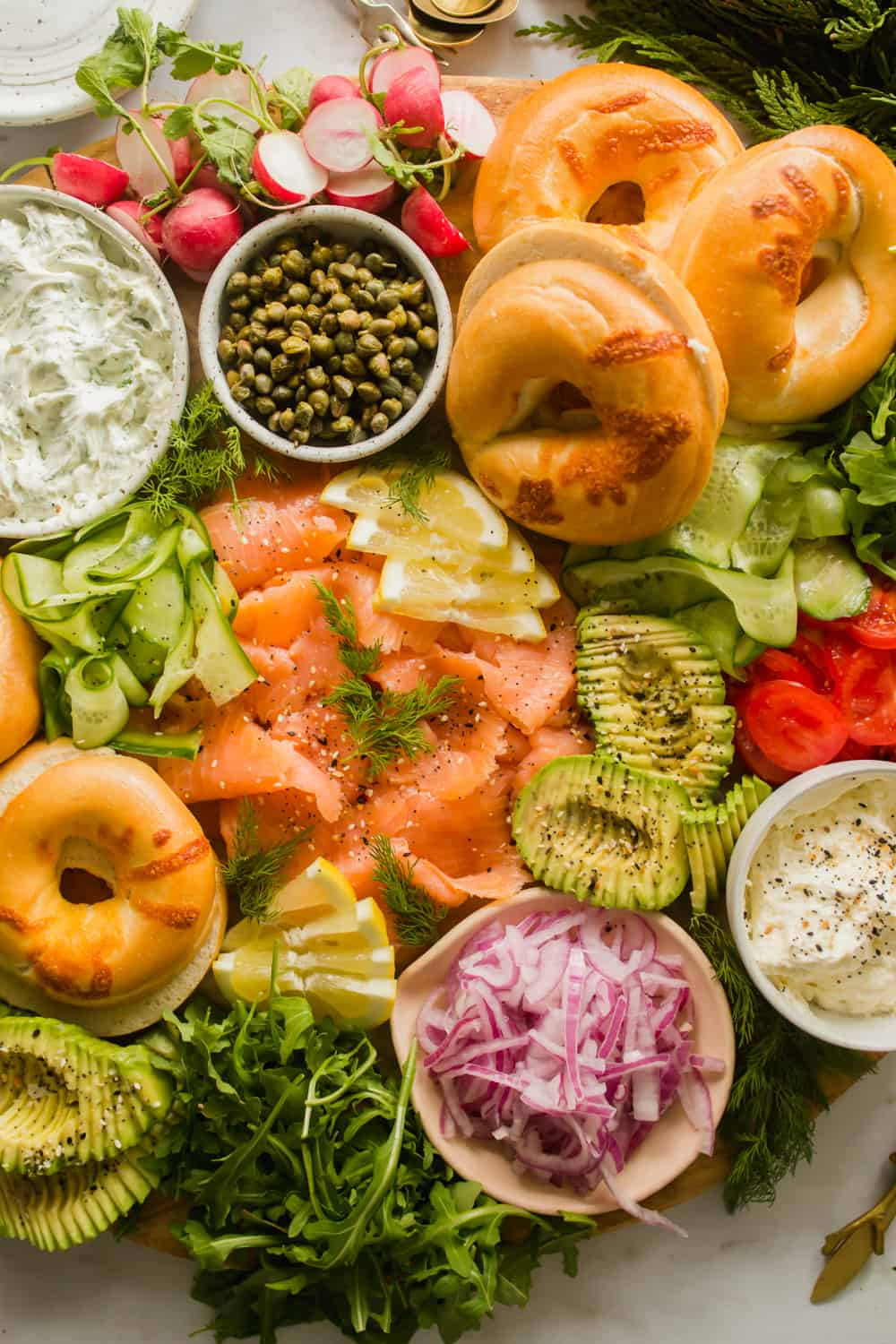 Close up of a large platter with bagels, lox, capers, vegetables, and cream cheese