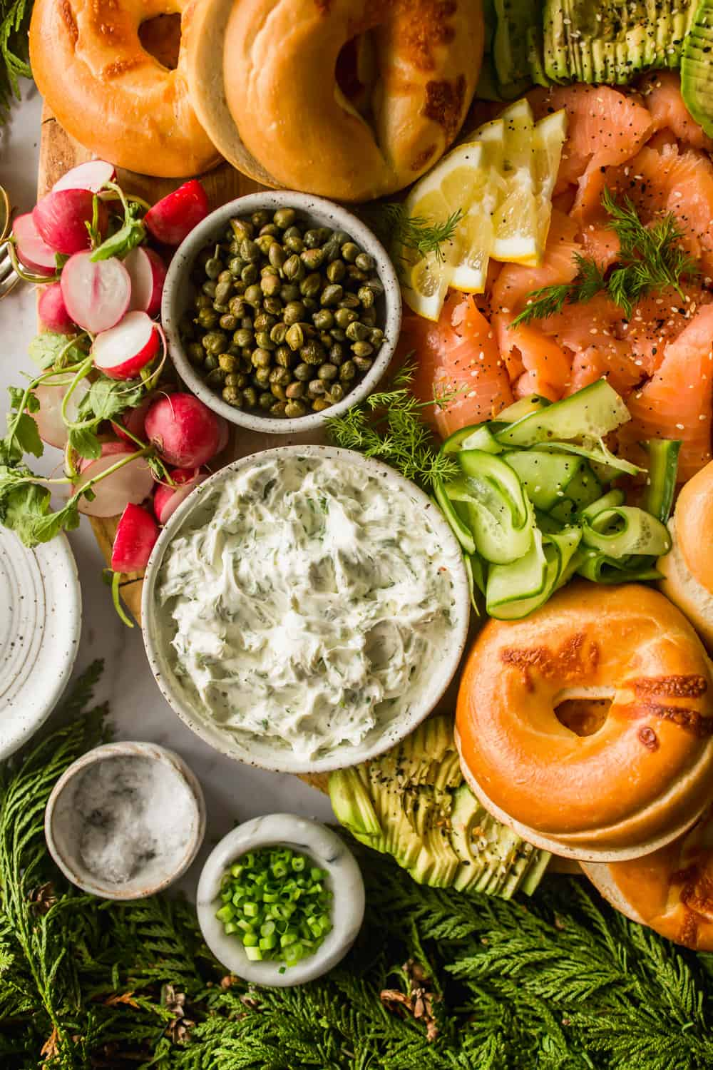 Close up of herbed cream cheese in a bowl next to a bowl of capers, bagels, salmon, and vegetables.
