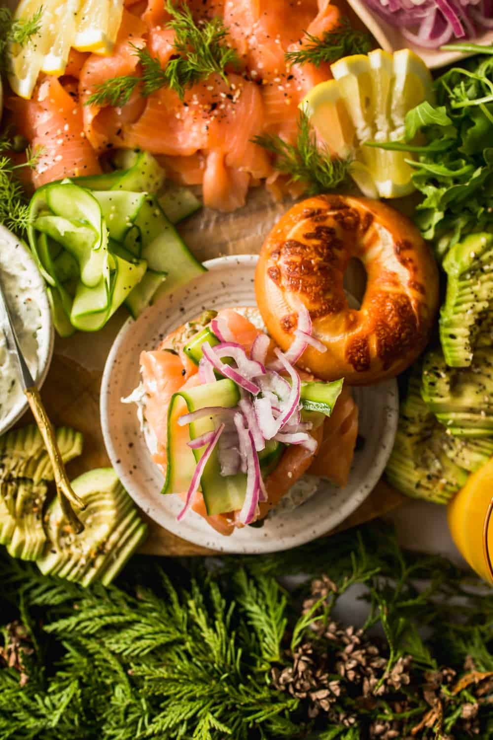 Close up of a bagel with salmon, cucumber, and onion on top