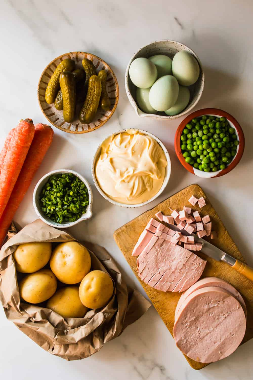 Pickles, eggs, peas, mayo, potatoes, scallions in individual bowls. Slicing ham on a wood cutting board.