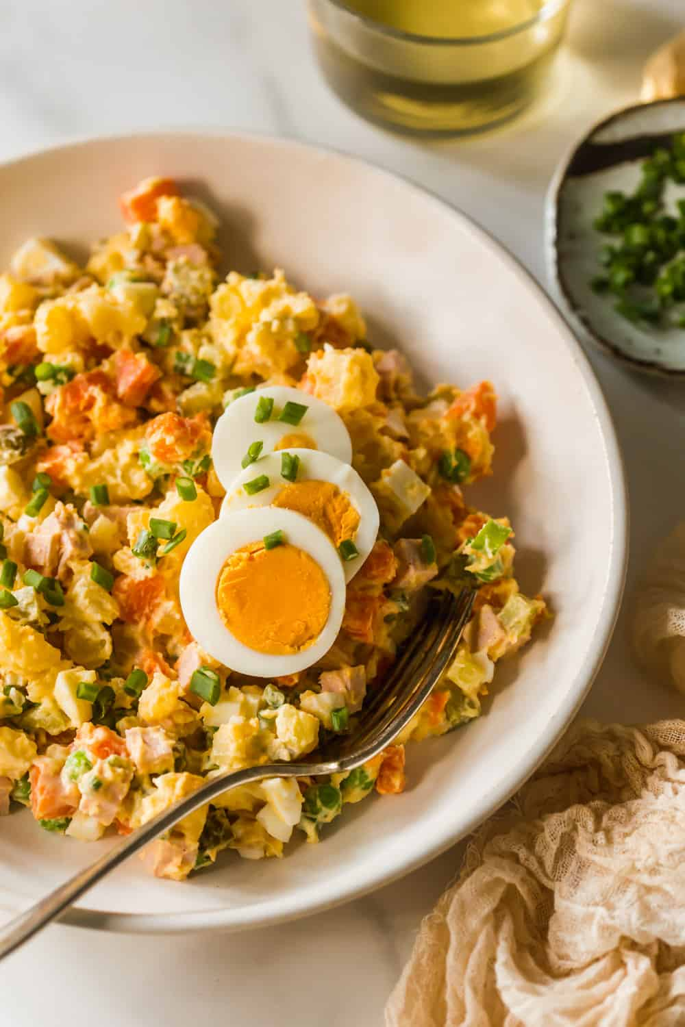 Yellow potato salad with sliced eggs on top in a large white bowl