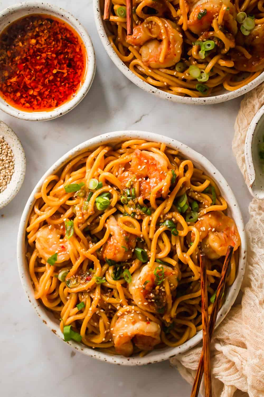 White bowl filled with yellow noodles, shrimp, and green onions. Small bowl with spicy sauce on the side.