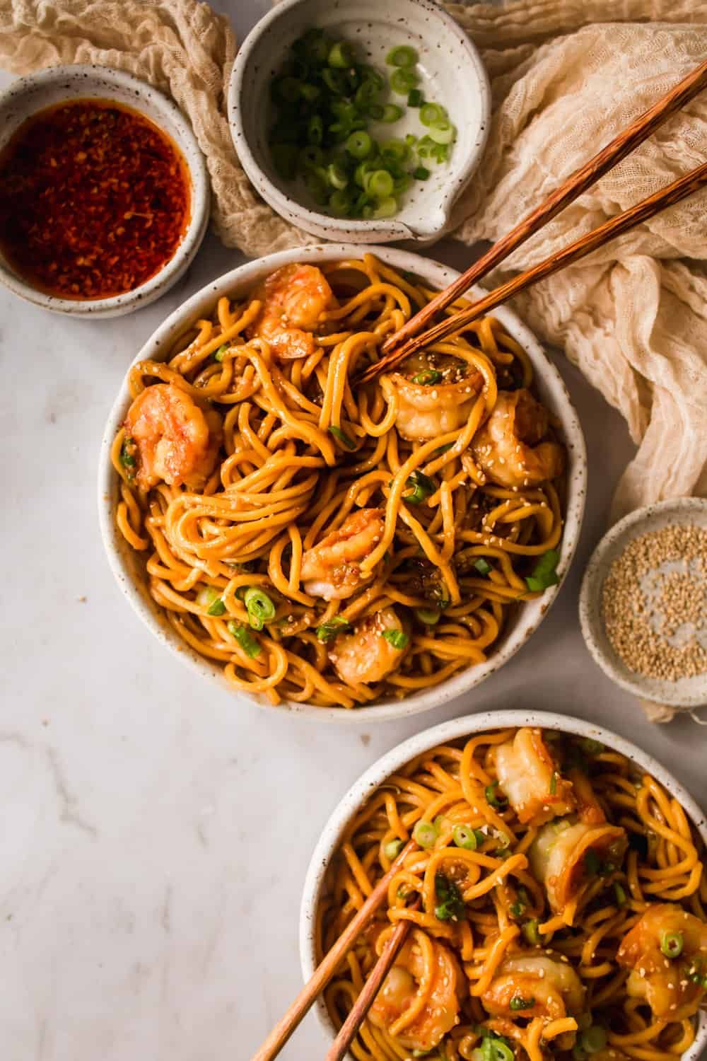 2 white bowls with yellow thin egg noodles, shrimp, and chopsticks. Small white bowls with green onions, oil, and sesame seeds on the side.