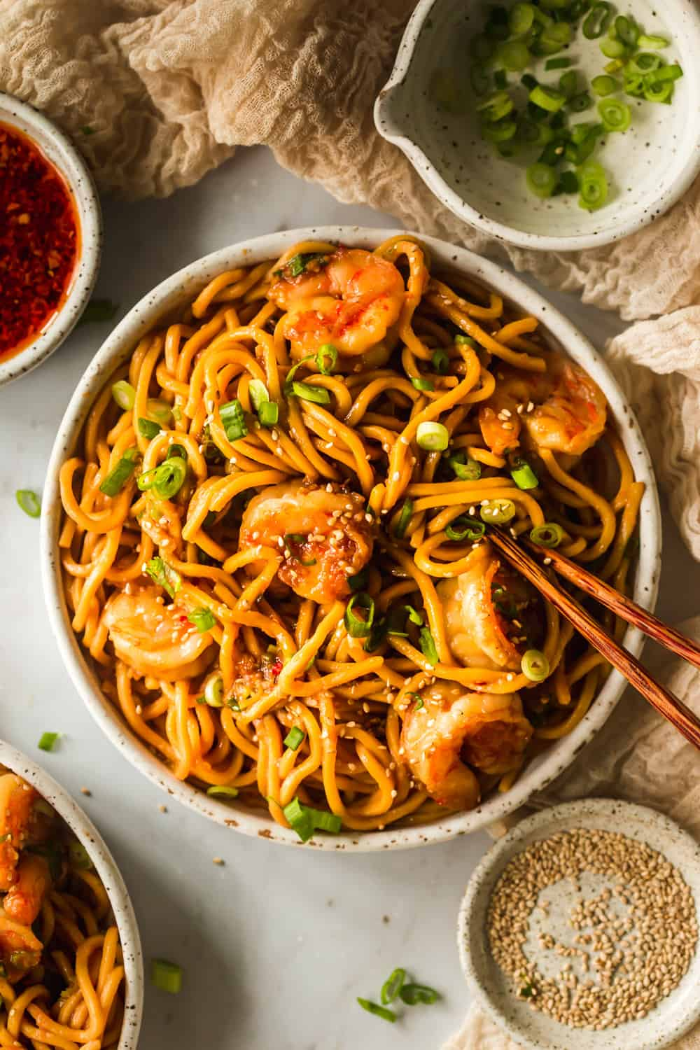 White bowl with yellow thin noodles, shrimp, and chopsticks