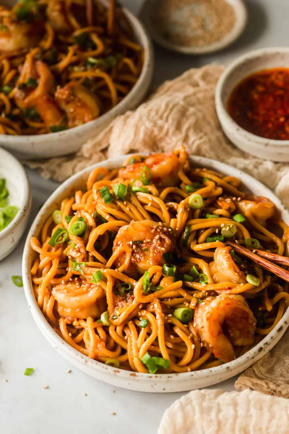 White bowl with yellow thin noodles, shrimp, and green onions on top.