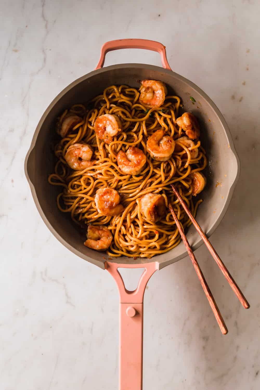 Large pan with long, thin noodles, shrimp, and chopsticks.