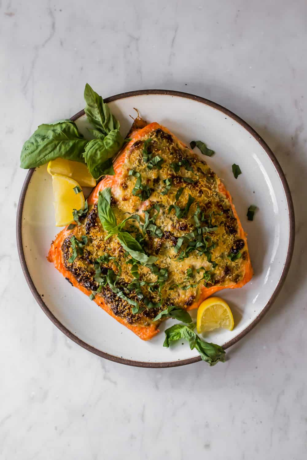 Coated fillet of salmon of a white plate with basil and lemon on the side