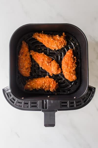 Orange buffalo chicken tenders in a black air fryer basket
