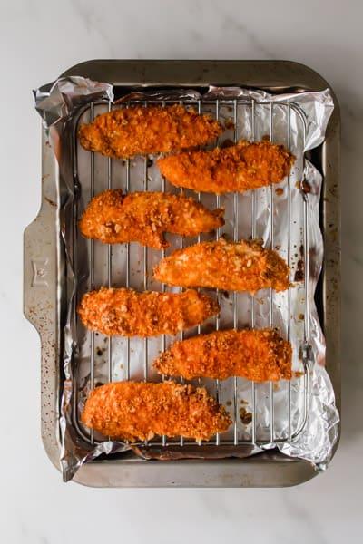 Orange buffalo chicken tenders on a metal baking rack