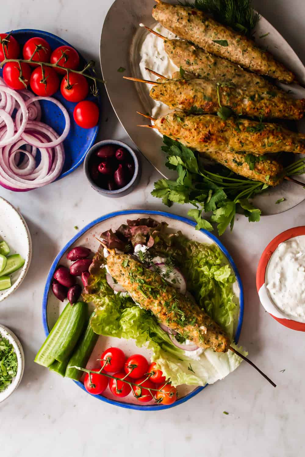 Chicken kebab on a white plate next to a large platter of kebabs and surrounded by lettuce, herbs, and fresh vegetables