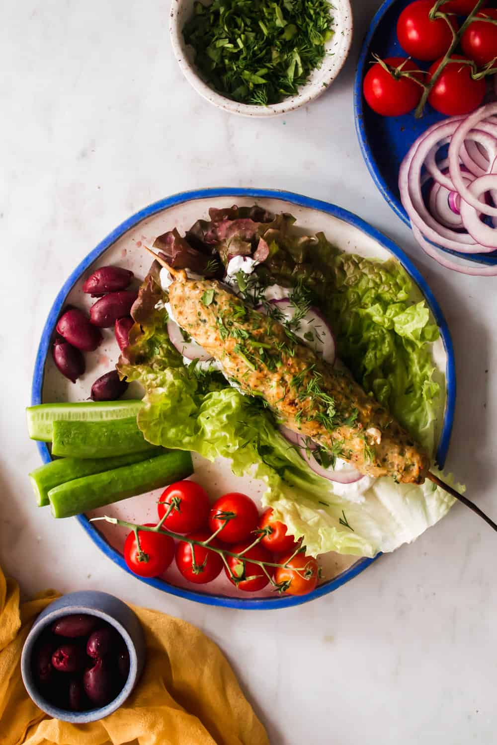 Chicken kebab on a white plate surrounded by lettuce, herbs, and fresh vegetables