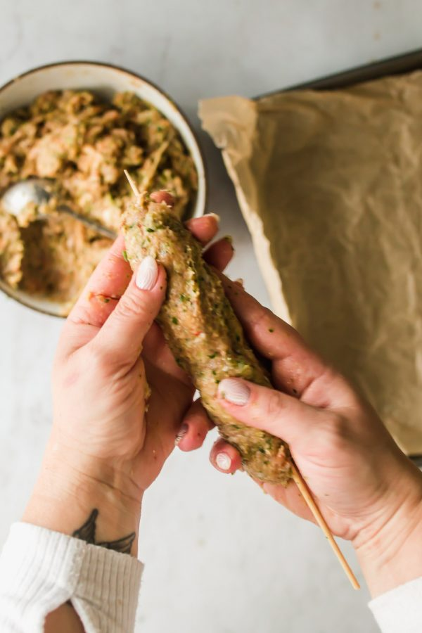 Woman's hand forming ground chicken around a wood skewer