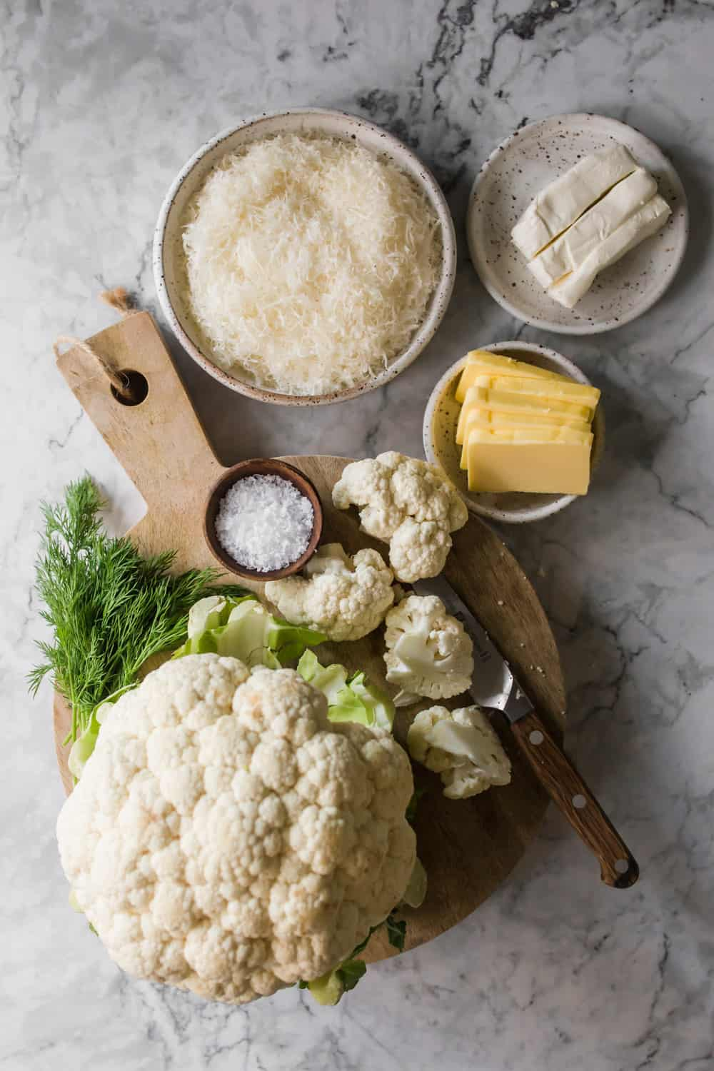 Chopping cauliflower on a wood cutting board. Small bowls with butter, cheese, and cream cheese on the side