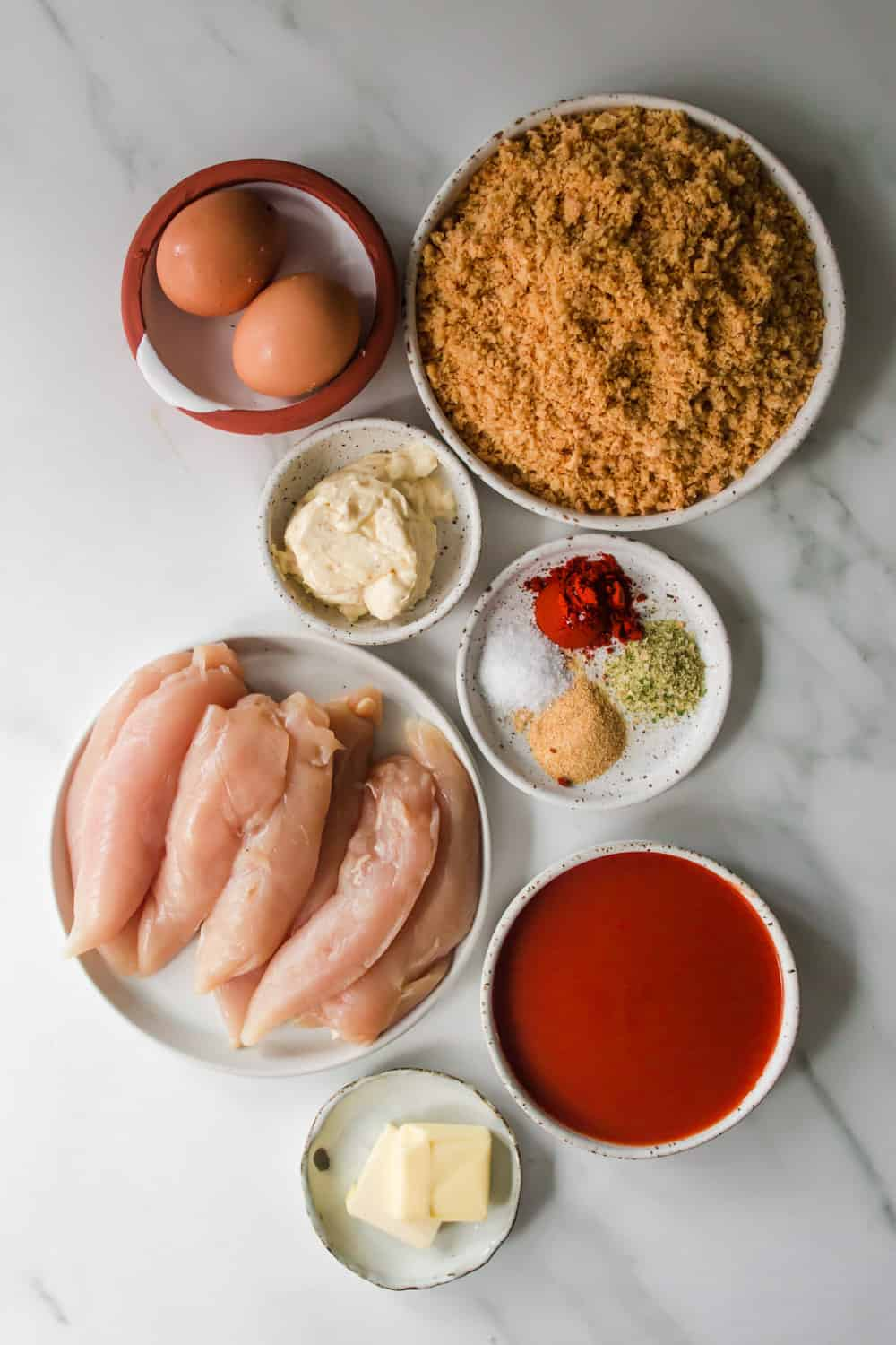 White individual bowls filled with raw chicken, buffalo sauce, spices, and eggs.