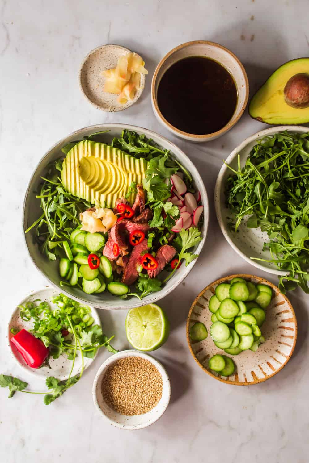 Individual small bowls filled with vegetables and ingredients for Asian salad. Large bowl with salad in the middle.