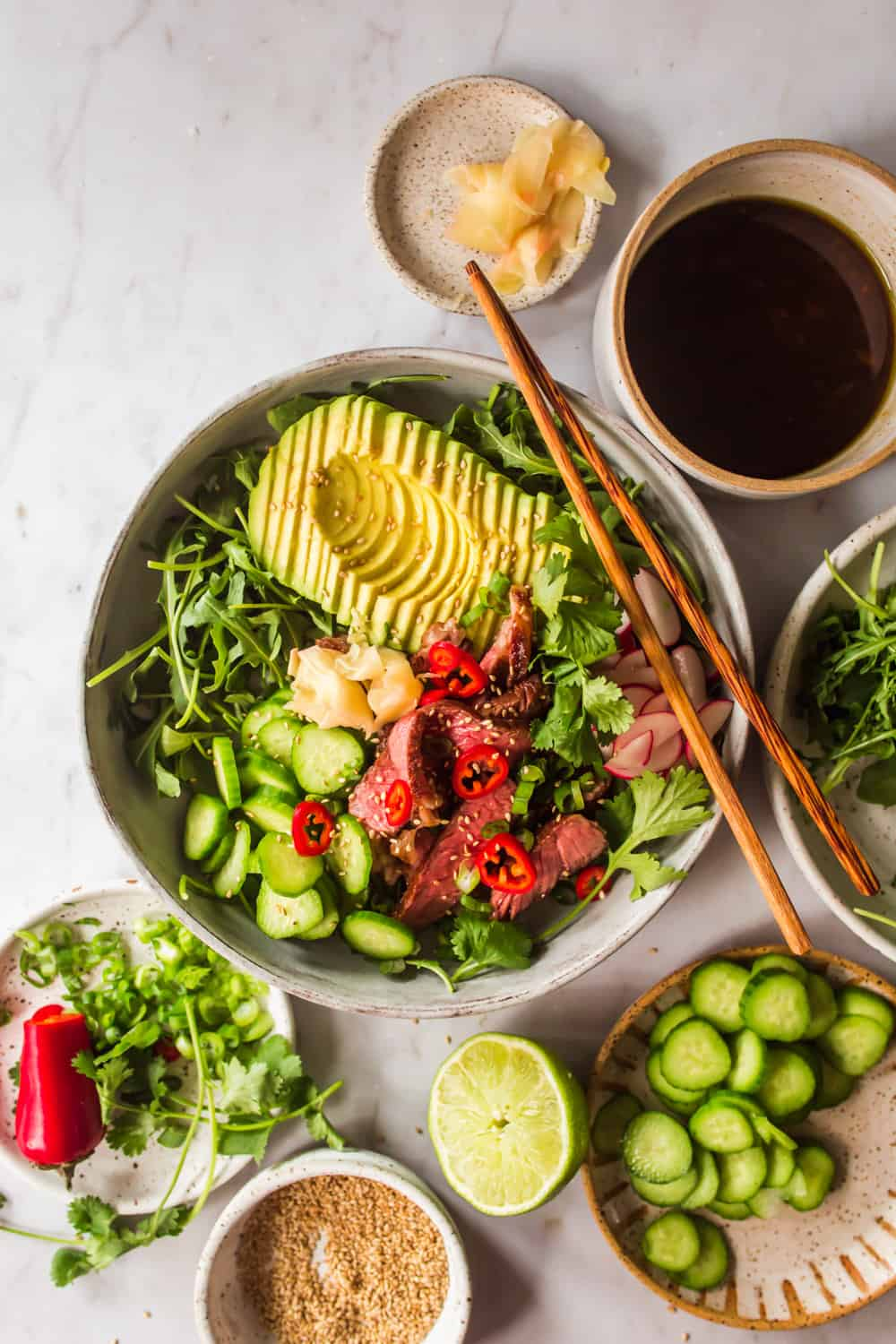 Large grey bowl with chopsticks filled with arugula, avocado, cucumber, steak, and vegetables. Small bowls with salad ingredients on the side.