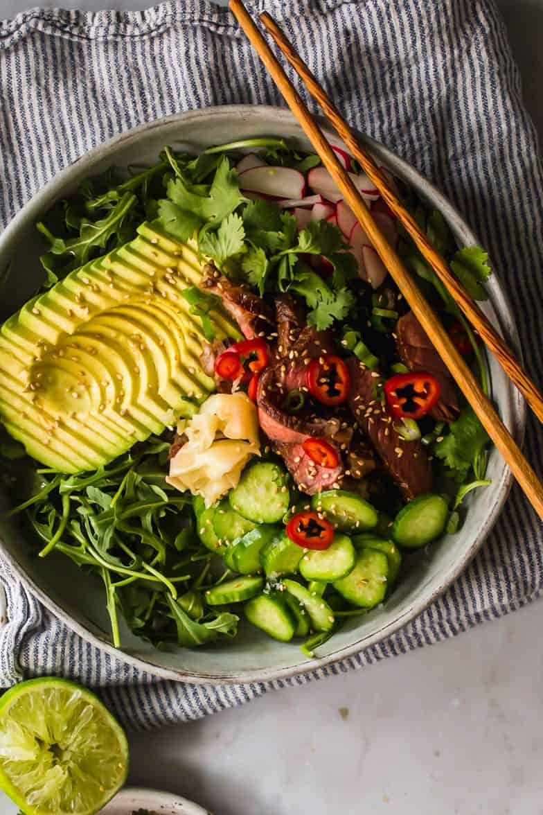 Close up of large grey bowl with chopsticks filled with arugula, avocado, cucumber, steak, and vegetables.