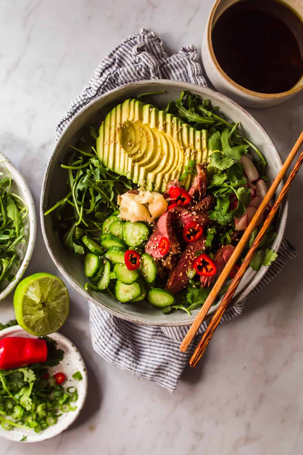 Large grey bowl with chopsticks filled with arugula, avocado, cucumber, steak, and vegetables.
