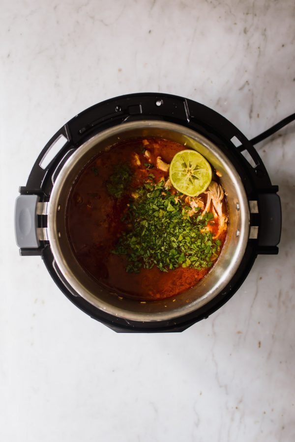 Herbs and lime on top of tomato-covered chicken in an Instant Pot