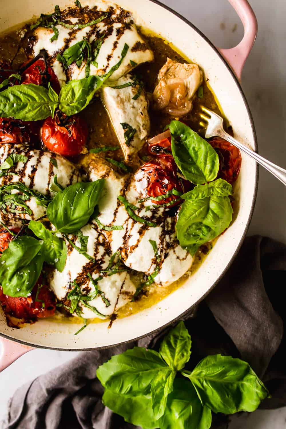 fork taking a piece of baked caprese chicken out of a pot