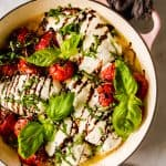 large pot with melted cheese on chicken with roasted tomatoes, basil, and balsamic on top