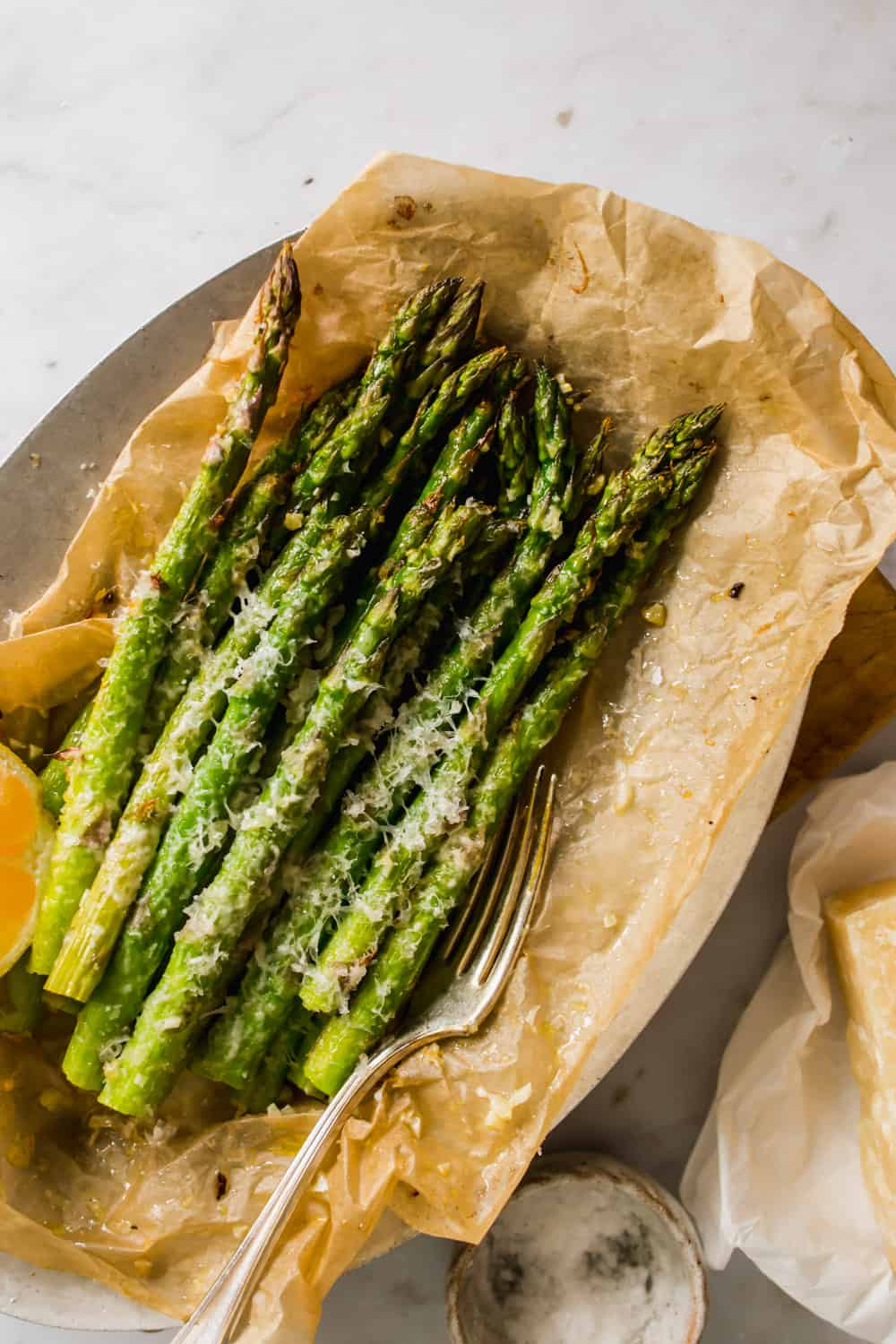 baked asparagus with cheese on top on a piece of parchment paper