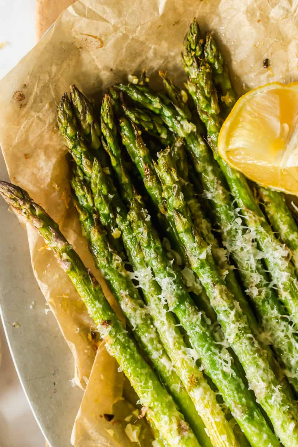 close up of baked asparagus with cheese on top next to a lemon wedge