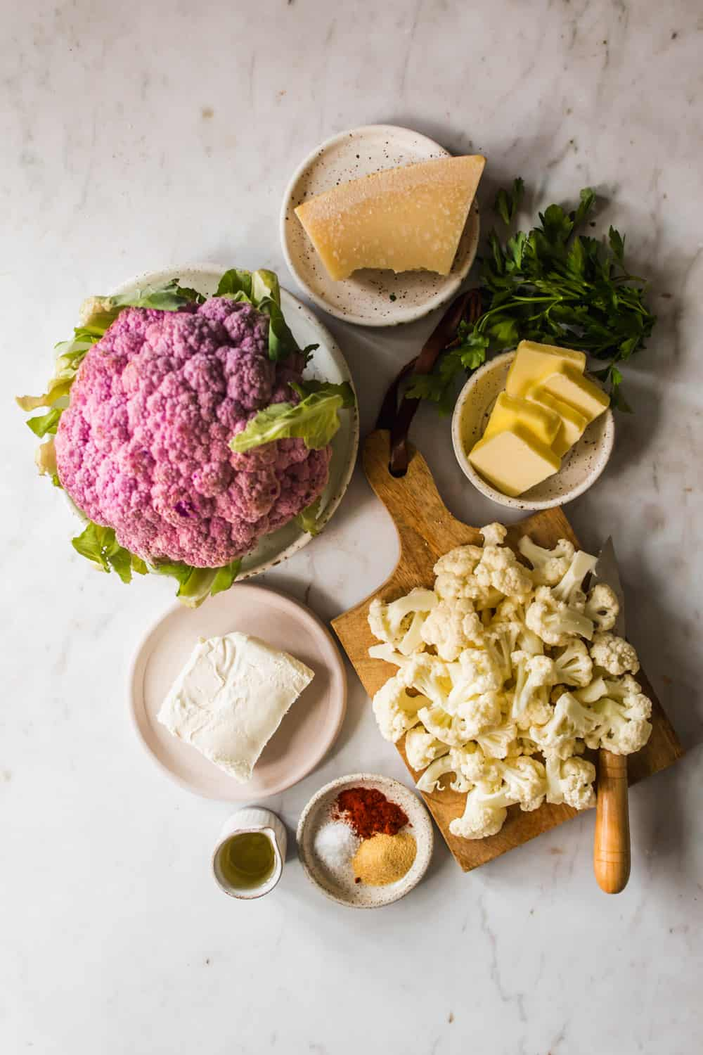 Head of purple cauliflower next to white cauliflower florets on a wood board. Small dishes with cheese and butter on the side.