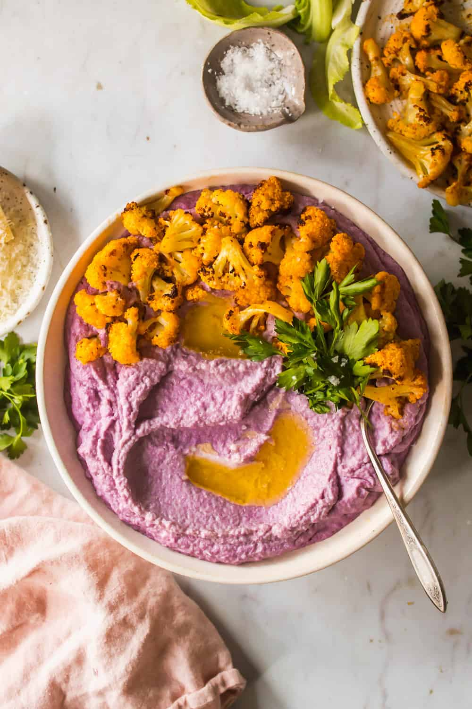 Large white bowl with mashed purple cauliflower, roasted cauliflower, and cilantro on top