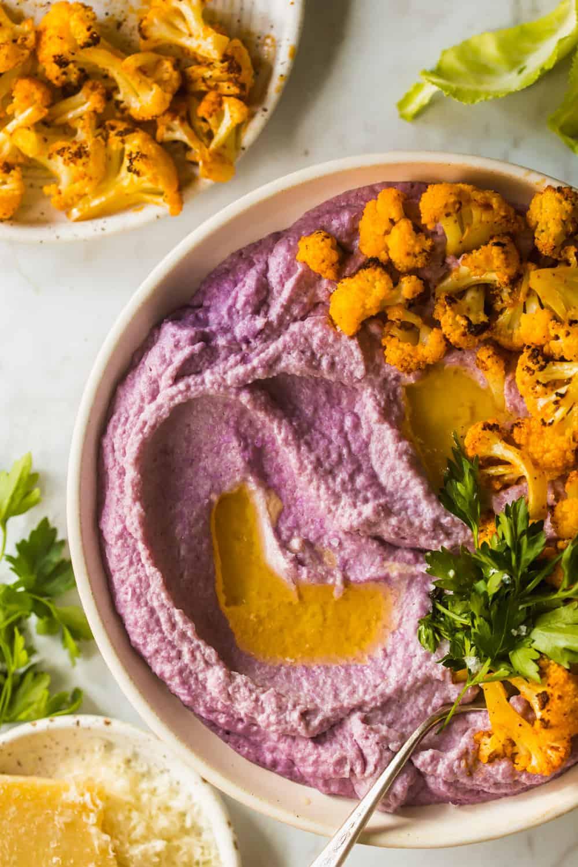 Large white bowl with mashed purple cauliflower, roasted cauliflower, and cilantro on top. Extra serving of roasted cauliflower on the side.