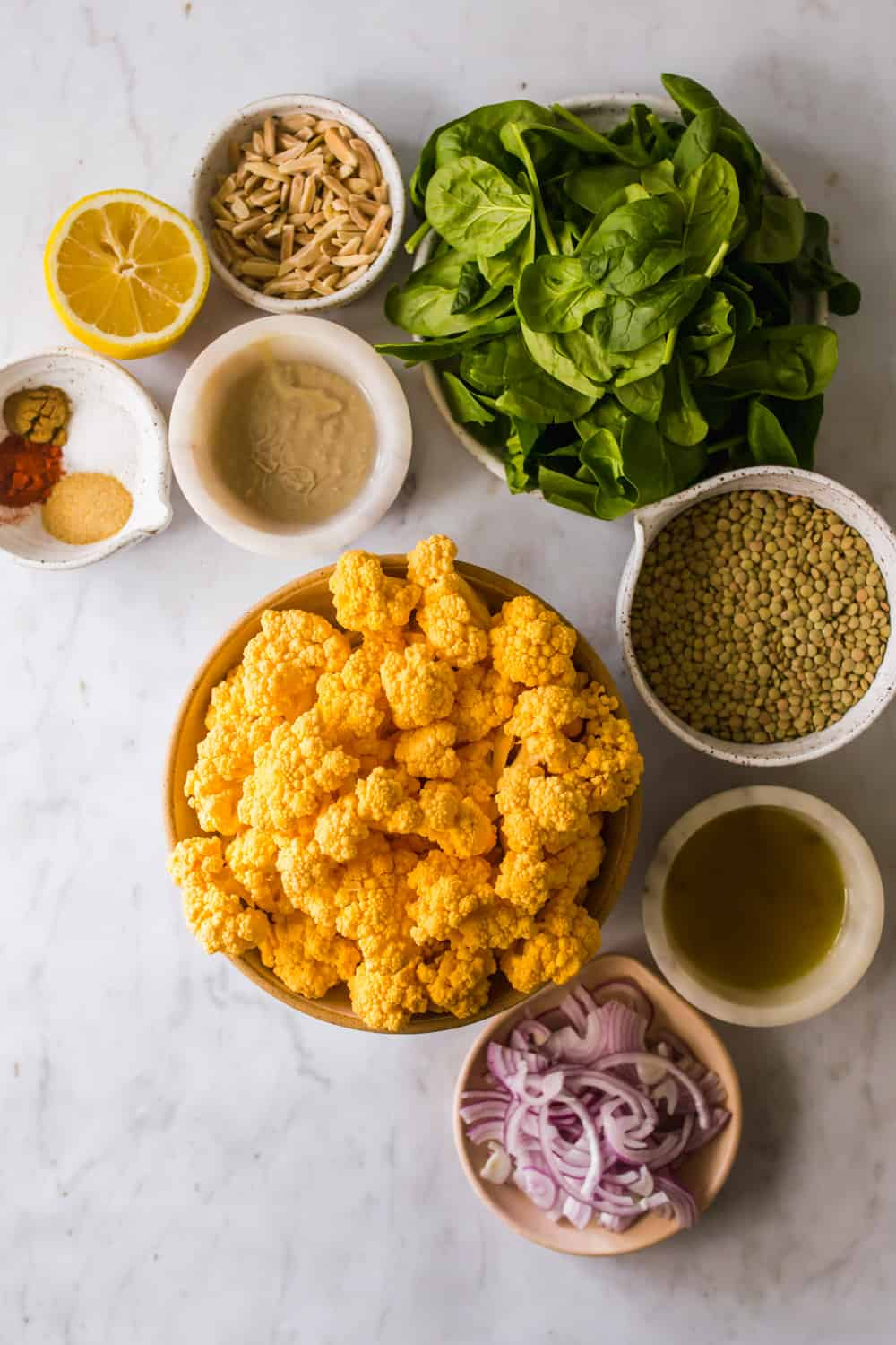 bowls of cauliflower, lentils, onions, greens, and salad dressing ingredients